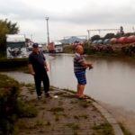 """Protest inedit la Aiud: Un bărbat a ieșit cu undița în fața gării din municipiu, la """"pescăria"""" formată după ploaie"""